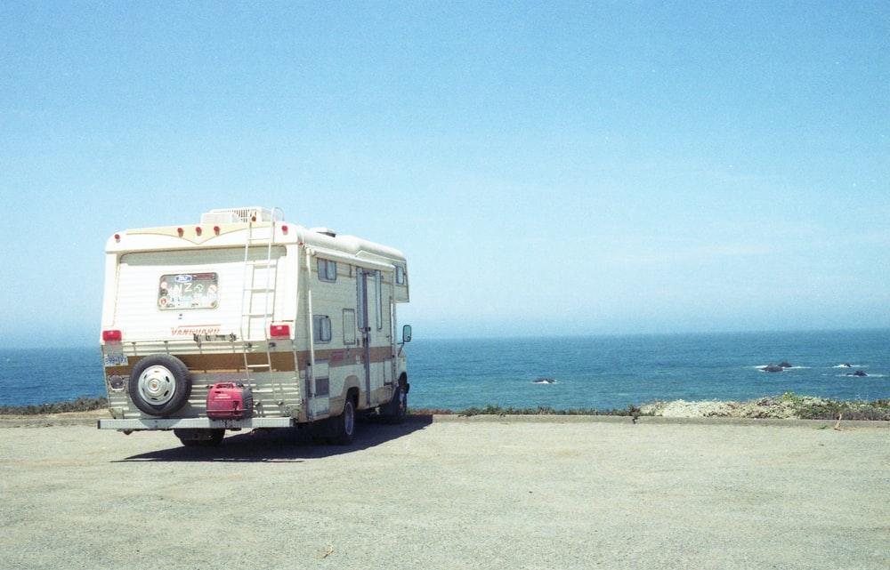 white and blue van on beach during daytime