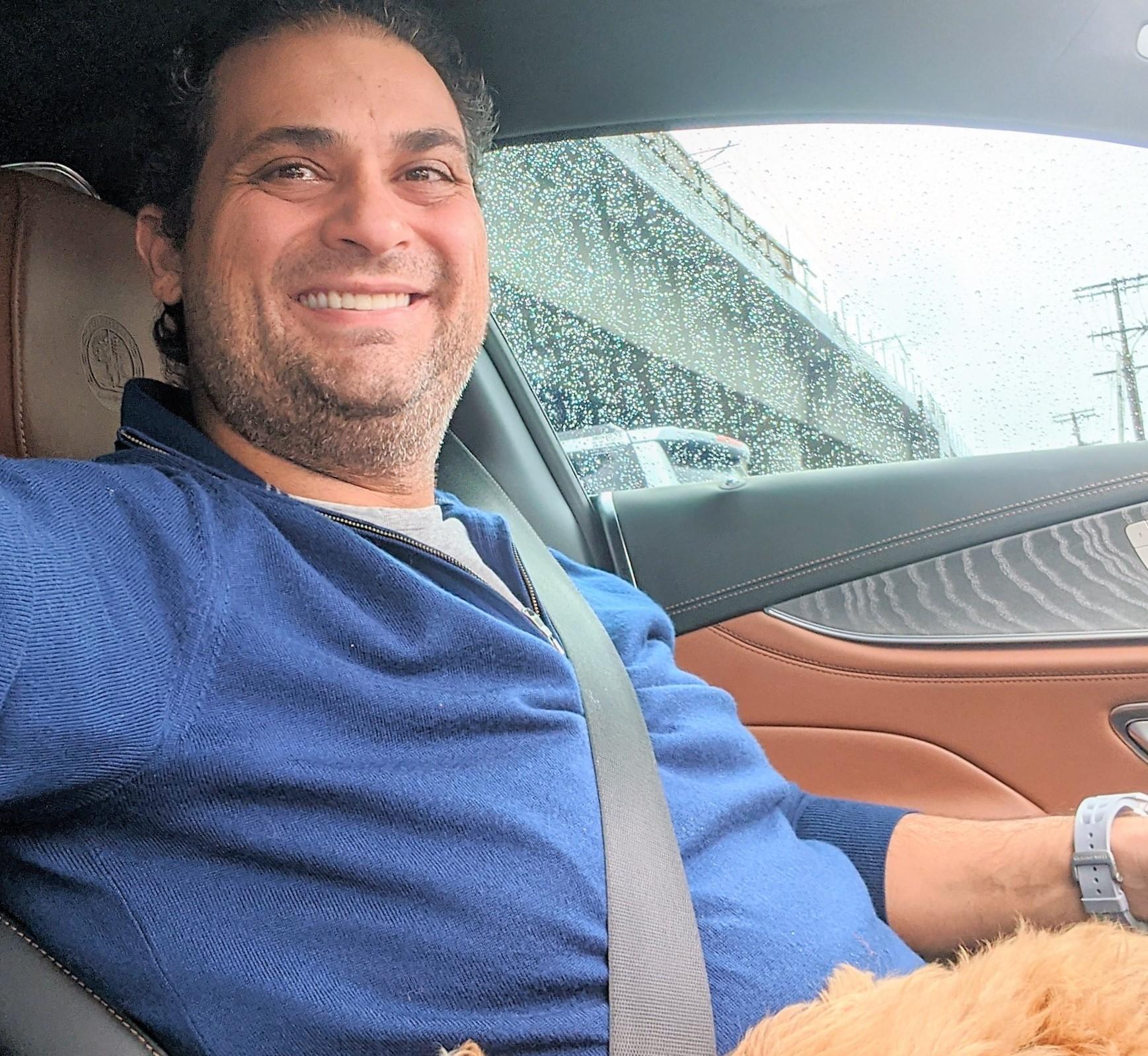 Dr. Navid Vahedi sitting in his car, smiling.