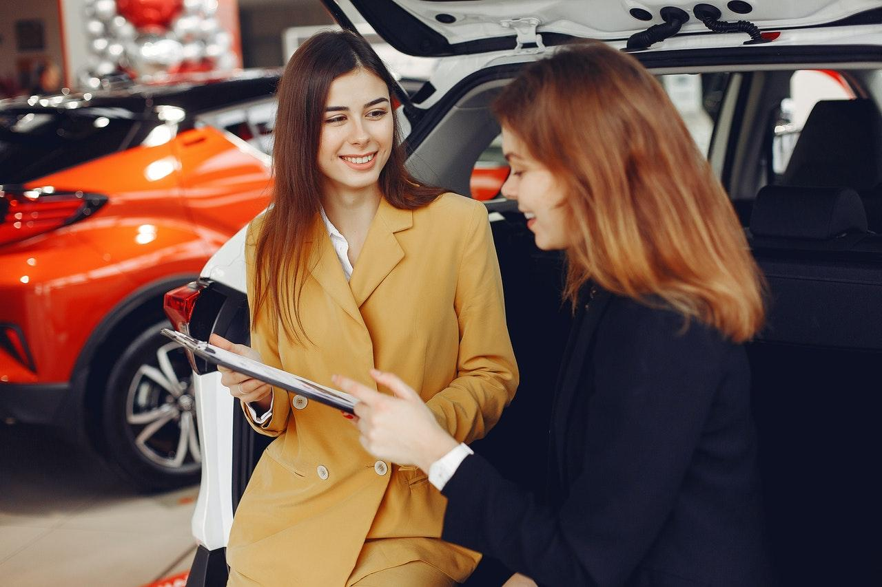 dealership personnel discussing the details of a car purchase with a customer