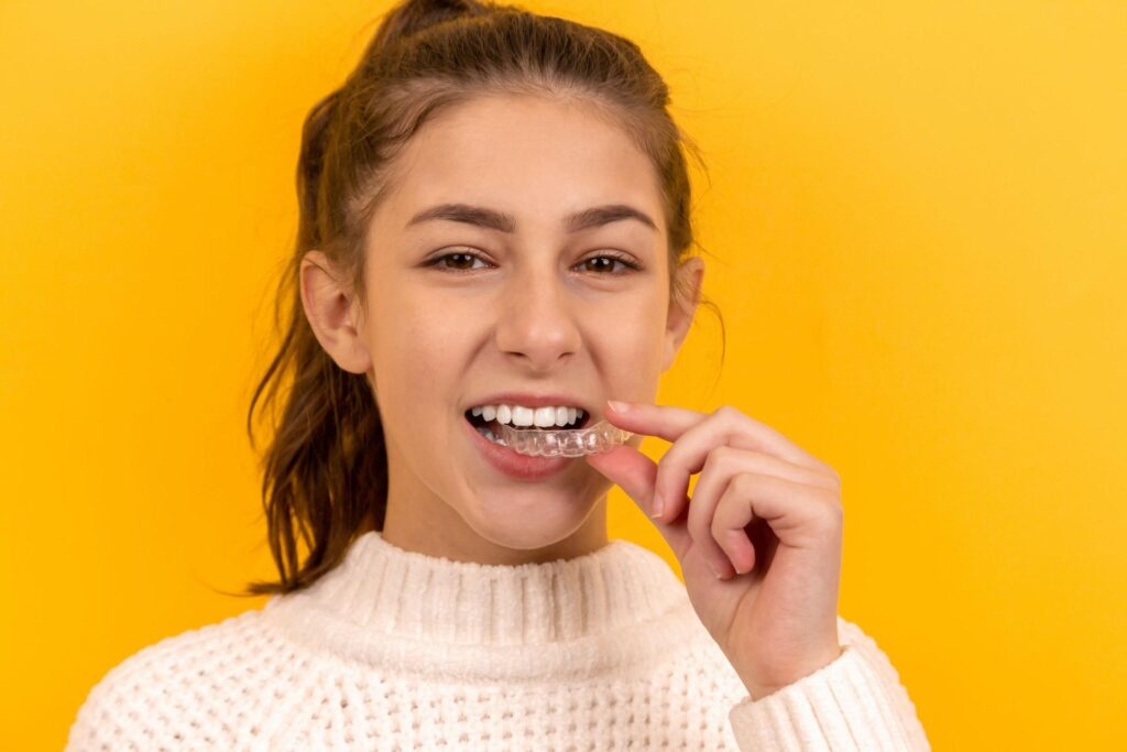girl using a clear aligner